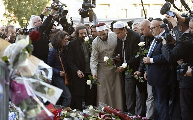 French author Marek Halter (4th left), imam of the Drancy Mosque, Hassen Chalghoumi (6th left), representatives of the Jewish and Muslim communities and others gather at a makeshift memorial near the Bataclan concert hall in Paris on November 15, 2015, two days after a series of deadly attacks. (AFP/Miguel Medina)