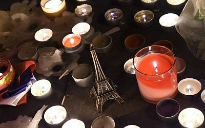 An Eiffel tower figurine is pictured among lit candles at a makeshift memorial in front of Le Carillon restaurant one of the sites of three deadly attacks in Paris, November 15, 2015. (AFP/DOMINIQUE FAGET)