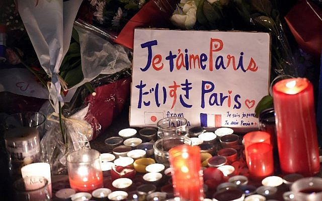 """A placard reading """"Paris I love you"""" is seen among candles at a makeshift memorial in front of the Bataclan theatre, one of the site of the attacks in Paris two days earlier, November 15, 2015 (AFP/FRANCK FIFE)"""