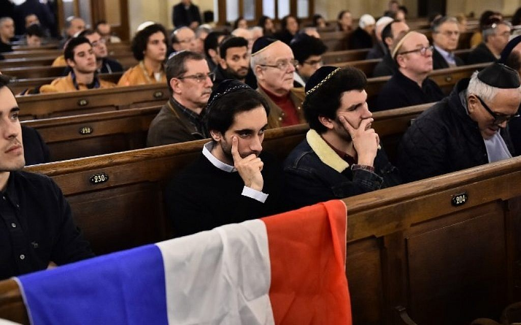 People sit near a French flag as they attend a ceremony for the victims of a series of deadly attacks at the Grande synagogue de la Victoire on November 15, 2015. (Loic Venance/AFP)