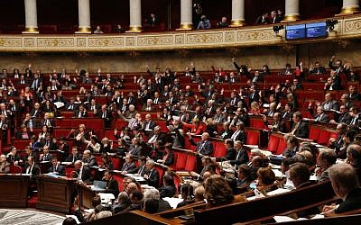 French MPs vote by a show of hands on an amendment during a debate on extending a state of emergency declared by the French president until the end of February, at the National Assembly in Paris on November 19, 2015. (Francois Guillot/AFP)