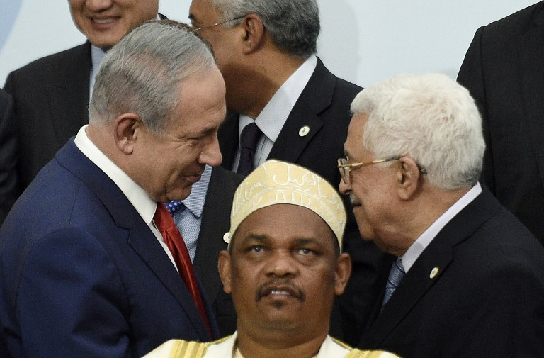 Prime Minister Benjamin Netanyahu (L) talks with Palestinian Authority President Mahmoud Abbas (R) behind Comoros' President Ikililou Dhoinine during the family photo during the COP21, United Nations Climate Change Conference, in Le Bourget, outside Paris, on November 30, 2015 (AFP PHOTO / POOL / MARTIN BUREAU)