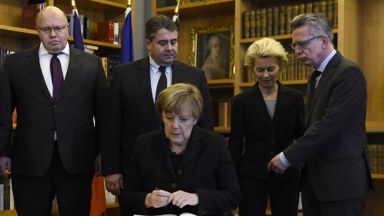German Chancellor Angela Merkel (C) signs a condolence book for the victims of deadly attacks in Paris a day before at the French Embassy in Berlin on November 14, 2015 (Tobias Schwarz/AFP)