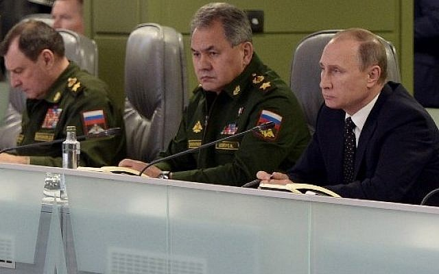 Russian President Vladimir Putin (R), accompanied by Defense Minister Sergei Shoigu (C), meets with top military officials at the National Defense Control Center of the Russian Federation in Moscow on November 17, 2015. (AFP PHOTO / SPUTNIK / ALEXEI NIKOLSKY)