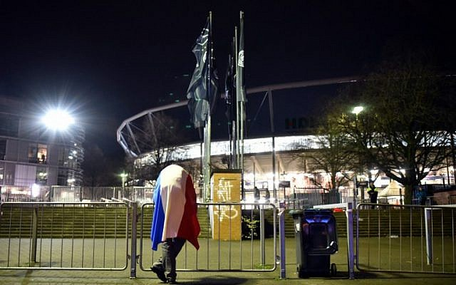 A football fan with a French flag stands outside a soccer stadium in Hanover, Germany after a game was called off for 'security reasons' in Hanover on November 17, 2015.  (AFP / DPA / OLE SPATA)
