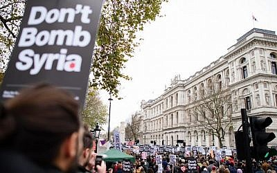 Demonstrators hold placards as they protest outside the entrance to Downing Street in central London on November 28, 2015, against the British government's proposed involvement in air strikes against the Islamic State group in Syria. (AFP/Leon Neal)