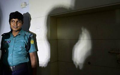 A Bangladeshi policeman stands guard at the office where publisher Ahmedur Rashid Chowdhury Tutul, blogger Tarik Rahim and writer Ranadipam Basu were attacked in Dhaka on October 31, 2015. (AFP Photo/Munir uz Zaman)