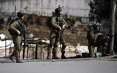 Israeli security forces stand in the street during clashes with Palestinian demonstrators in the West Bank city of Hebron, on October 30, 2015. (AFP/Thomas Coex, File)