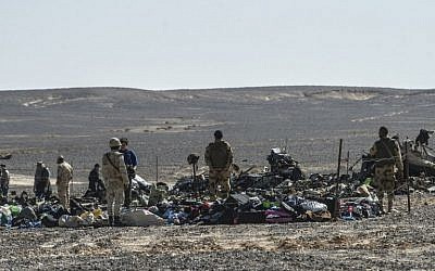 Egyptian army soldiers stand guard next to debris and belongings of passengers of the A321 Russian airliner that crashed the previous day in Wadi al-Zolomat, a mountainous area in Egypt's Sinai Peninsula, on November 1, 2015. (AFP PHOTO / KHALED DESOUKI)