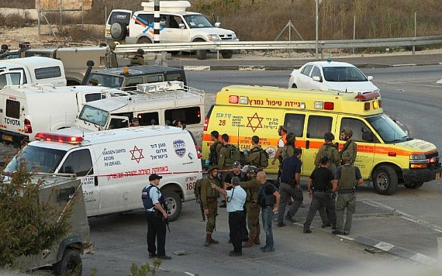 File: Israeli security forces and emergency personnel gather at the site of a reported car-ramming attack on Israeli Border Policemen at the Beit Anun junction, north of the West Bank city of Hebron, on November 1, 2015. (AFP/Hazem Bader)