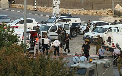 Israeli security forces and emergency personnel gather at the site of a reported car-ramming attack on Border Police at the Beit Einun junction, north of the West Bank city of Hebron, on November 1, 2015. (AFP/Hazem Bader)