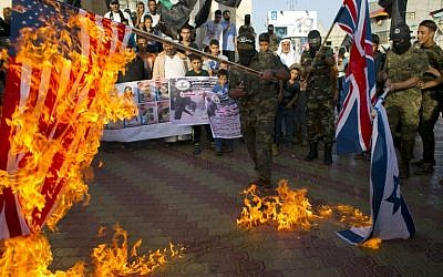 Palestinian militants burn the British, US and Israeli flags during a demonstration to mark the anniversary of the Balfour Declaration in the southern Gaza Strip town of Rafah on November 2, 2015. (AFP PHOTO/SAID KHATIB)