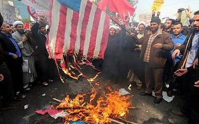 Iranians burn a US  flag outside the former US embassy in Tehran on November 4, 2015, during a demonstration marking the anniversary of its storming by student protesters that triggered a hostage crisis in 1979. (AFP PHOTO / ATTA KENARE)