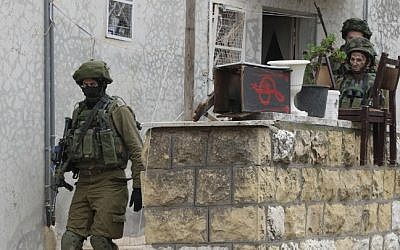 Israeli soldiers search a Palestinian home in the West Bank town of Hebron, November 7, 2015. (AFP/Hazem Bader, File)