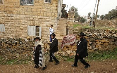 Ultra-Orthodox Jews walk past Israeli soldiers conducting a search on a Palestinian home in the West bank town of Hebron on November 7, 2015. (AFP/HAZEM BADER)