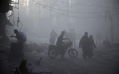 Syrians walk in a dusty street following air strikes by suspected Russian planes on the central rebel-held town of Douma, on the outskirts of the capital Damascus, on November 7, 2015. (AFP/ABD DOUMANY)