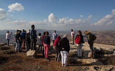 Nati Rom, chairman of Lev Haolam foundation, guides a group European Christians during a tour of the Israeli outpost of Esh Kodesh in the West Bank on November 10, 2015. (Menahem Kahana/AFP)
