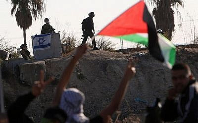 Palestinian protesters wave their national flag during clashes with members of the Israeli security forces in the West Bank city of Tulkarem on November 12, 2015. (Jaafar Ashtiyeh/AFP)