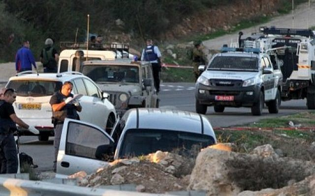 Israeli soldiers and police inspect a car following a deadly attack near the settlement of Otniel, south of the West Bank city of Hebron, on November 13, 2015. (AFP/Hazem Bader)