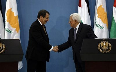 Cypriot President Nicos Anastasiades and PA President Mahmoud Abbas shake hands during a joint press conference in the West Bank city of Ramallah on November 13, 2015. AFP PHOTO/POOL/ALAA BADARNEH)