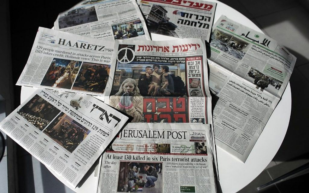 Palestinian and Israeli newspapers bearing the headlines of the deadly Paris attack that left more than 120 people dead, in the worst such violence in France's history, November 15, 2015  (Photo by AFP Photo / Ahmad Gharabli)