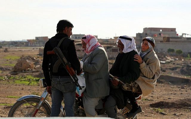 Syrians on a bike stop at a checkpoint monitored by a member of the internal Kurdish security forces in the Al-Shallal suburb of Al-Hol on November 19, 2015, after Syrian Democratic Forces took control of the area from Islamic State. (AFP PHOTO/DELIL SOULEIMAN)
