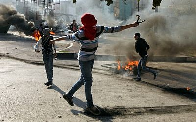 Illustrative: Palestinian protesters throw stones towards Israeli security forces during clashes in the West Bank city of Hebron on November 20, 2015. (AFP/Hazem Bader)