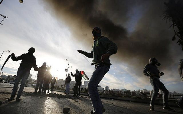 Illustrative: Palestinians throw stones at Israeli security forces during clashes in the Palestinian town of al-Bireh on the outskirts of Ramallah on November 20, 2015. (AFP Photo/Abbas Momani)
