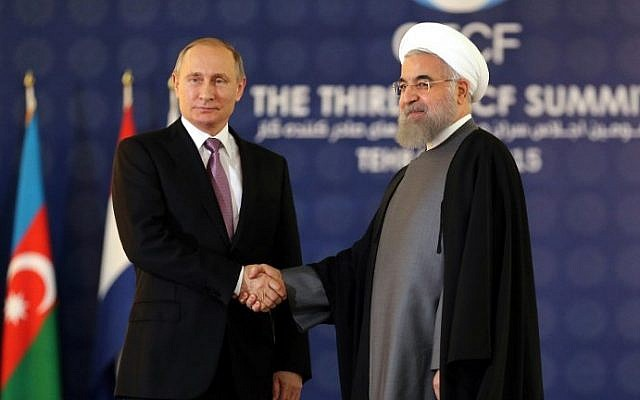 Iranian President Hassan Rouhani shakes hands with his Russian counterpart Vladimir Putin during the Gas Exporting Countries Forum (GECF) summit in Tehran on November 23, 2015. (AFP PHOTO / ATTA KENARE)
