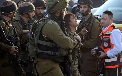 An Israeli female soldier reacts at the scene of a stabbing attack carried out by a Palestinian man against two Israeli soldiers, killing one of them, at a gas station on a main road on the busy 443 highway, November 24, 2015. (AFP/Gil Cohen-Magen)