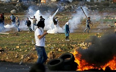 Palestinian demonstrators hurl rocks at Israeli security forces during clashes in al-Bireh on the outskirts of Ramallah in the West Bank, on November 29, 2015.  (AFP/Abbas Momani)