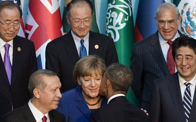 US President Barack Obama greets German Chancelor Angela Merkel, center, alongside Japanese Prime Minister Shinzo Abe, right, Turkish President Recep Tayyip Erdogan, left and other world leaders as they stand for the official family photo during the G20 summit in Antalya, Turkey, November 15, 2015. AFP/SAUL LOEB)