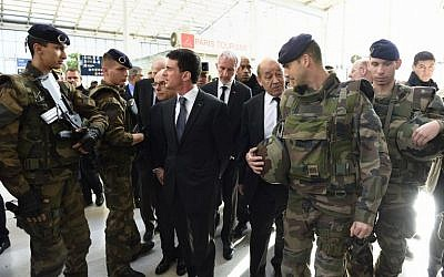 French Prime minister Manuel Valls, center, arrives with French Defense minister Jean-Yves Le Drian and other officials at the Gare du Nord railway station in Paris on November 15, 2015, to speak with SNCF staff about security measures following a series of coordinated attacks in and around Paris on November 13. (AFP/ERIC FEFERBERG)