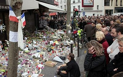 People observe a minute of silence on November 16, 2015, outside the La Belle Equipe on Rue de Charonne in the XI Arrondissement in Paris, to pay tribute to victims of the attacks claimed by Islamic State, which killed at least 129 people and left more than 350 injured on November 13, 2015. (AFP/Jacques Demarthon)