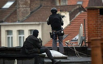Special force officers stand guard on a roof top near the scene of a police raid in Rue Delaunoy, in the district of Molenbeek, in Brussels on November 16, 2015. (AFP PHOTO/BELGA/DIRK WAEM)