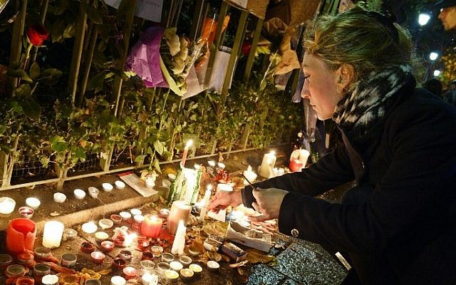 A woman lights candles at a makeshift memorial next to the Bataclan concert hall on November 16, 2015 in Paris. (AFP/ BERTRAND GUAY)