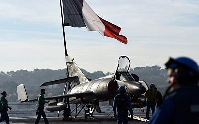 A French flag flies above French naval technicians working on the flight deck of the aircraft carrier Charles de Gaulle at a military port in the southern French city of Toulon, on November 18, 2015, before leaving in Eastern Mediterranean Sea. (AFP PHOTO / ANNE-CHRISTINE POUJOULAT)