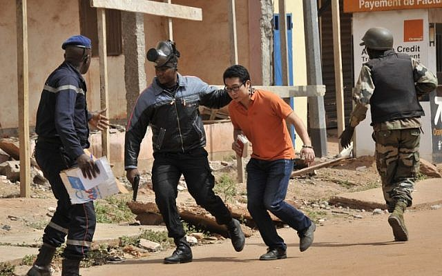 Malian security forces evacuate a man from an area surrounding the Radisson Blu Hotel in Bamako on November 20, 2015. (AFP/Habibou Kouyate)