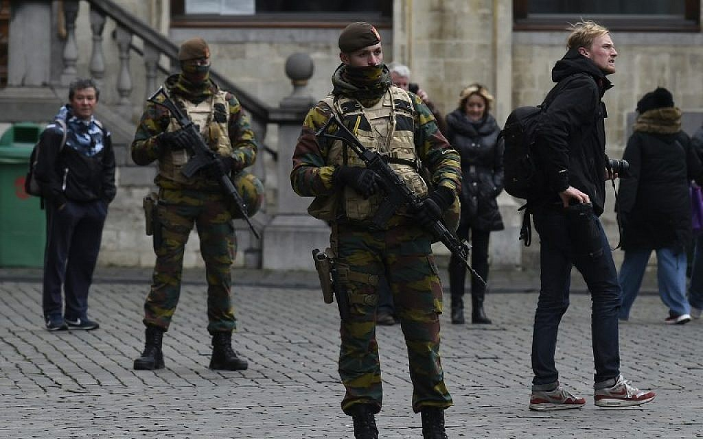 Belgian soldiers stand at the Grand Place in Brussels on November 22, 2015. The Belgian capital was locked down for a second day on November 22 with police and troops on the streets as the authorities hunted for several suspects linked to the Paris attacks. (Photo by AFP Photo/John Thys)