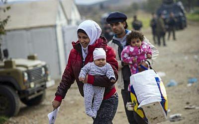 Migrants and refugees cross the border between Greece and Macedonia near Gevgelija on November 22, 2015. (AFP PHOTO / ROBERT ATANASOVSKI / AFP / ROBERT ATANASOVSKI)