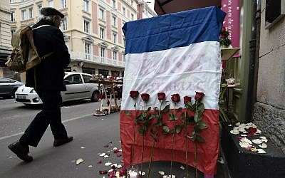 A man walks past a French national flag put outside a flower shop on November 27, 2015 in Strasbourg, eastern France, in tribute to the 130 people killed in the November 13 Paris attacks. (AFP Photo/Frederick Florin)