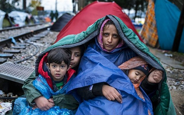 A woman and her children look on as migrants and refugees wait to cross the Greece-Macedonia border in the rain on November 27, 2015 near Gevgelija. (AFP PHOTO / ROBERT ATANASOVSKI / AFP / ROBERT ATANASOVSKI)