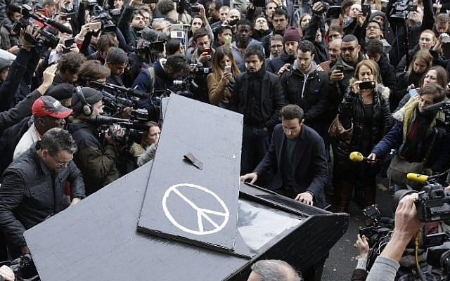 A man plays piano near the cordened off area around the Bataclan theatre in the 11th district of Paris on November 14, 2015, after a series of attacks on the city resulting in the deaths of at least 120 individuals. (AFP PHOTO / KENZO TRIBOUILLARD)