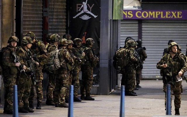 French army soldiers stand in position in the northern Paris suburb of Saint-Denis, on November 18, 2015, as French Police special forces raid an appartment, hunting those behind the attacks that claimed 129 lives in the French capital five days ago. (AFP PHOTO/KENZO TRIBOUILLARD)