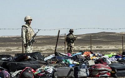 Egyptian army soldiers stand guard next to the luggage and belongings of passengers of the A321 Russian airliner piled up at the site of the crash in Wadi el-Zolmat, a mountainous area in Egypt's Sinai Peninsula on November 1, 2015. (AFP PHOTO/KHALED DESOUKI)