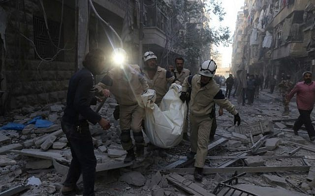 Syrian emergency personnel carry a body following an air strike on November 3, 2015, in the rebel-held side of the northern city of Aleppo. (Baraa al-Halabi/AFP)