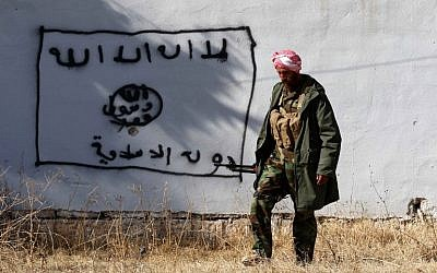 A Kurdish fighter walks by a wall bearing a drawing of the flag of the Islamic State (IS) group in the northern Iraqi town of Sinjar, in the Nineveh Province, on November 13, 2015. (AFP/SAFIN HAMED)