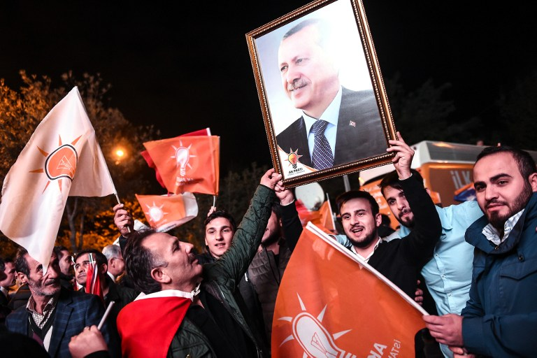 Supporters of Turkey's Justice and Development Party (AKP) hold up a portrait of Turkish President Recep Tayyip Erdogan as they celebrate in Istanbul after the first results in the country's general election on November 1, 2015. (Photo by AFP Photo / Ozan Kose)
