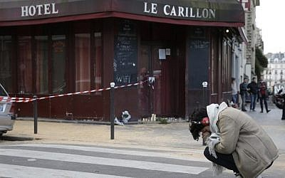 A woman mourns outside of the Carillon bar in the 10th district of Paris on November 14, 2015, following a series of attacks in and around the city, leaving at least 120 people killed. AFP PHOTO / KENZO TRIBOUILLARD