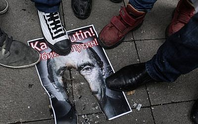 Turkish protesters walk over a burnt poster depicting Russian President Vladimir Putin and reading 'Putin, killer!' during an anti-Russia demonstration in Istanbul, November 27, 2015. (AFP/Cagdas Erdogan)